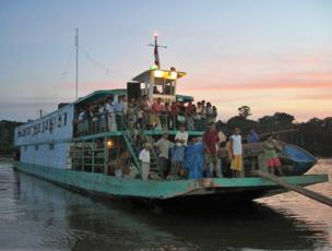 A ferry full of people travels along a river in Amazonian Peru