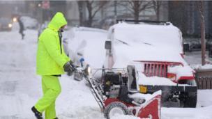 pria sedang membersihkan salju