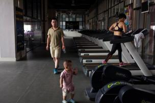Huang Wensi's husband Deng Peipeng, looks after their son while accompanying her on a training session in a local gym