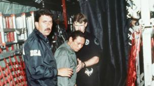 Panamanian General Manuel Noriega (C) is brought on board a US military plane 3 January 1990 for a flight to Miami after his arrest.