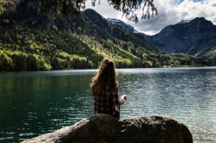 A girl looks out over Lake Langbathsee, Austria