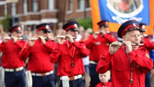 Uniformed band flautists playing and marching in a parade