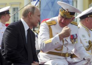 شهد الرئيس الروسي فلاديمير بوتين (يسار) العرض البحري وإلي جانبه قائد القوات البحرية الروسية الأميرال نيكولاي يفمينوف (يمين).