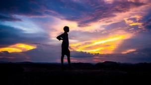 Silueta de un niño sobre una montaña