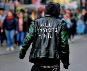 A man wearing a leather jacket with 'All Systems Fail' written on the back