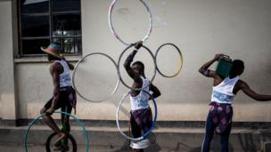 Congolese acrobatic performers dey wait for dia turn to perform on top of stage during di Amani Festival.