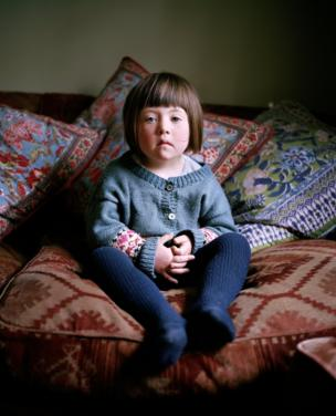 A small girl sits on the sofa and looks in to the camera
