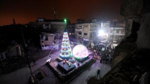 Humus kentindeki Hamidiye mahallesinde 24 Aralık olan Noel akşamı insanlar yıkık evlerin arasında bir araya geldiler
