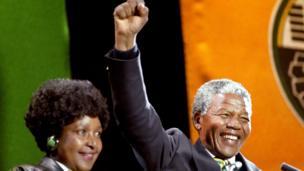 Nelson Mandela, iyo xaaskiisii xilligaasi Winnie,oo u gacan haadinaya taageerayaasha xisbiga ANC fagaaraha Wembley 17 April 1990