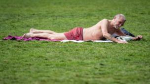"""رجل يستغل درجة الحرارة العالية للاستمتاع بحمام شمس في حديقة """"غرين بارك"""" في لندن"""