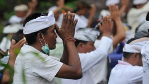 Balinese Hindus take part in a ceremony, where they pray near Mount Agung in hope of preventing a volcanic eruption, in Muntig village