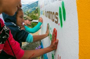 A Farc guerrilla fighter helps children paint a peace mural in Santa Lucia, July 2016.