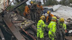 Firefighters rescue a girl after she was trapped inside a destroyed home during heavy rains in Montecito, California.