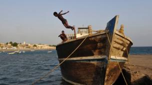 Young boys dive into the sea from a boat, on March 25, 2016 in Tadjoura, north central Djibouti.