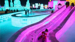 People visit the ice sculptures illuminated by coloured lights at Harbin ice and snow world for the 33rd Harbin International Ice and Snow Festival in Harbin city, China's northern Heilongjiang province, 05 January 2017.