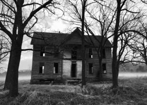 Una casa abandonada entre árboles.