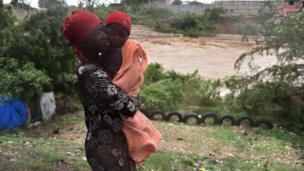 Mama ambeba mwanawe, wakati zoezi la kuhamisha raia likiendela kutokana na hatari ya mto ulio karibu kuvunja kingo zake, katika mji mkuu wa Haiti, Port-au-Prince, tarehe 4 , Oktoba 2016