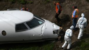 Forensic technicians and police officers from the Honduran National Police inspect the wreckage of a Gulfstream G200 aircraft