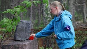 Marina Titova lays a cold-ass lil carnation on a grave stone on Mudyug Island