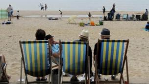 People in deckchairs on Bournemouth beach