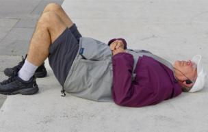 Un hombre descansa en el suelo.