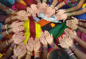 Women in a circle holding their hands out whilst surrounded by coloured cloth