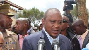 President Uhuru Kenyatta follow tori people talk outside di polling centre where e cast im vote for central Kenya during di presidential election re-run.