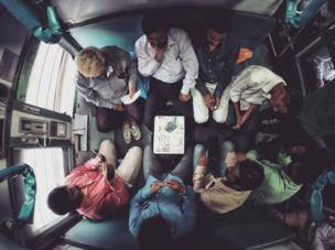 Passengers playing cards on a train.