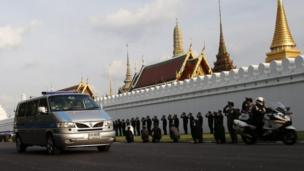 A convoy of vehicles carries the body of the Thai king