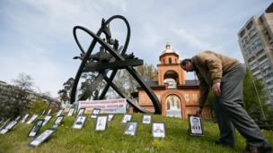 Портреты ликвидаторов у мемориала жертвам Чернобыльской катастрофы в Киеве