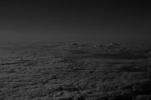 Clouds are photographed from above in black and white.