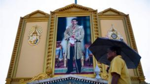 A man walks past a portrait of Thailand's King Maha Vajiralongkorn near the Grand Palace in Bangkok on May 3