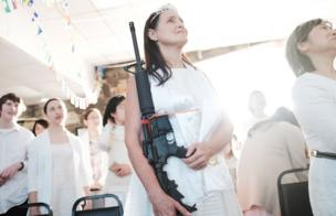 A woman holds an AR-15 rifle during a ceremony at the World Peace and Unification Sanctuary on February 28