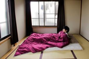 Minimalist Katsuya Toyoda demonstrates how he sleeps in his room in Tokyo