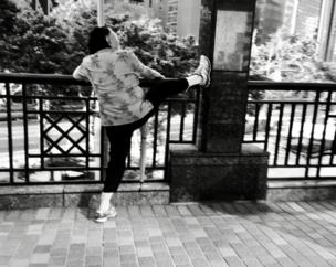 A woman stretches her leg on the railings in a park
