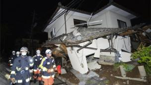 Firefighters check the damage of the collapsed house in Mashiki, near Kumamoto city, southern Japan, after the earthquake early Friday, April 15, 2016.