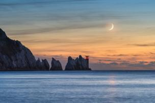 """القمر في هيئة الهلال ليلا فوق فنار """"نيدليس"""" الواقع على الحافة الغربية لجزيرة وايت الإنجليزية"""