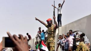 Members of the Sudanese military gather in a street in central Khartoum on April 11, 2019, after one of Africa's longest-serving presidents was toppled by the army.