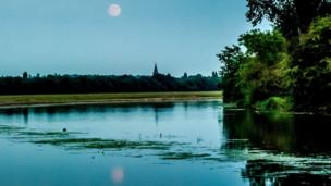 A full moon rises over Port Meadow, Oxford. The tower of the St Phillips and St James church, Woodstock Road, is in the background.