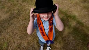 "5 year old Issac Kelly adjusts his father""s bowler hat on his head as the Independent Orange Lodge holds their annual parade on July 12, 2017 in Rasharkin, Northern Ireland"