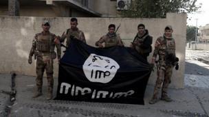 กองกำลังอิรักถือป้ายผ้าสีดำสัญลักษณ์ของไอเอสกลับหัว