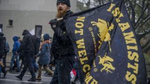 """ﻳﻜﻲ اﺯ شرکتگنندگان در راهپیمایی ﺑﺎ ﭘﺮﭼﻢ ﺿﺪ اﺳﻼم که نوشته است """"اسلامگراها اینجا جایی ندارند"""""""