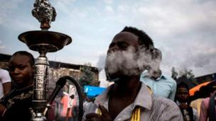 One of di Congolese festival-goer smoke from hookah during di Amani Festival wey dem do inside Goma.