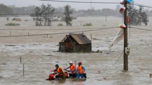 Người dân dắt xe máy qua cánh đồng ngập trắng ở Hà Tĩnh, nơi bão Doksuri tràn qua hôm 15/9/2017.