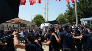 Turkish police hold their batons as people shout at government officers and police during the funeral of victims of the attack at a wedding party 21/08/2016