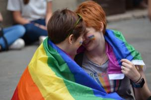 A couple are wrapped in a rainbow flag