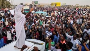 """The day before, an icon of the protests, Alaa Salah, who has been nicknamed the """"Nubian queen"""", speaks to crowds in Khartoum."""