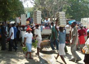 In a busy market, people carry towering egg cartons on their heads