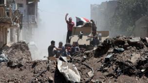 نازحون من مدينة الموصل القديمة يحاولون اجتياز حاجز ترابي من بقايا المتاريس في مناطق القتال بمساعدة عربة مدرعة للجيش العراقي