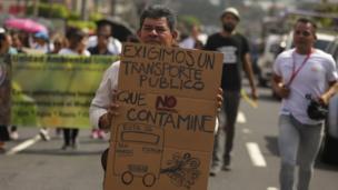 """Un hombre sostiene un cartel demandando """"transporte público que no contamine"""". en San Salvador."""
